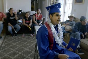 A male student in a blue graduation cap and gown and flower neckless sits among a group of people in a living room.