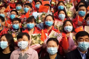 A group of people all wearing face masks waving the Chinese flag.