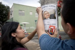 """A Latinx woman with black hair and someone off screen hang a poster that reads """"MISSING PERSON."""" It has a picture of a Latinx man with short black hair on it."""