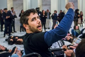 A white man with brown hair and facial hair raises his fist in the air. He is in a wheelchair.