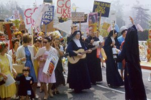 A group of people protesting, including several nuns in black robes.