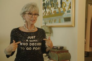 """An older white woman with gray hair and black glasses. She is pointing to her shirt which reads """"Just A Girl Who Decided To Go For It."""""""