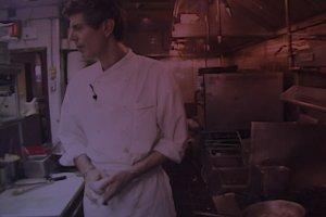 Anthony Bourdain, an older white man with short hair wearing a white chef's coat, stands in a small kitchen.