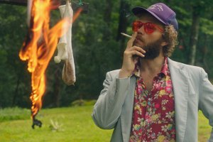 A white man with brown hair and facial hair wearing red shades and a Hawaiian shirt and blazer. He smokes a cigarette and watches socks burn.