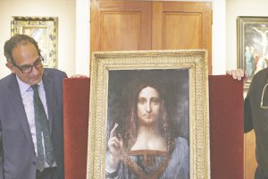 An older white man with black glasses and gray short hair stands next to Salvator Mundi, a painting of a white man with long brown hair pointing upwards.