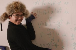A young Asian student with glasses, wearing a goofy fur hat, motions to a white board with a math formula on it.