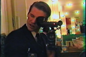 A white man with short brown hair holds a camera up to a mirror.