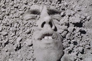 A black and white portrait of a white man submerged in dirt. David Wojnarowicz, Untitled (Face in Dirt), 1991. © Estate of David Wojnarowicz. Courtesy of the Estate and P·P·O·W.