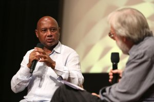 Raoul Peck speaking into the mic facing with Kenneth Turan