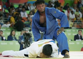 A Congolese Judo fighter looms over his defeated opponent in the Olympic arena