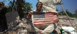 An Indonesian man holds a tattered American flag in a trash heap.