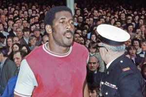 Clyde Best walks through the pitch at West Ham United, with a sea of fans in the stands behind him