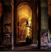 a man welds in the graffitied arches of what appears to be an old church.