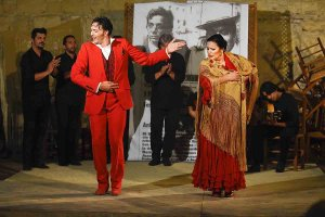 Two flamenco dancers receiving applauses on stage.