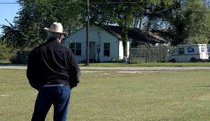 A man in a brown wide-rimmed hat stands facing a white rural house.