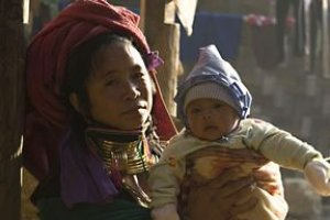 An Asian woman in an elaborate headscarf and necklaces holds her infant child.