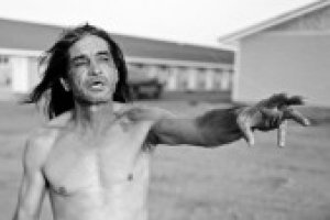 Black and white photograph of a shirtless Native American man reaching his arm out in mid-speech