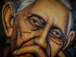 A close-up of a painting of a wrinkled face of an old woman.