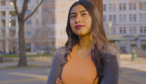 A young Latina woman stands with arms crossed in front of distant buildings