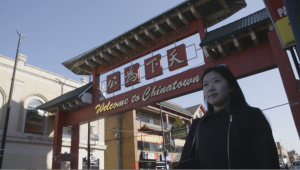 Chinese American woman stands in front of the gate of New York City's Chinatown.