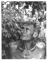 Black and white portrait of Alan Chadwick in front of a plant.