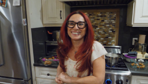 A red-haired Armenian-American smiles at the camera in a home kitchen.