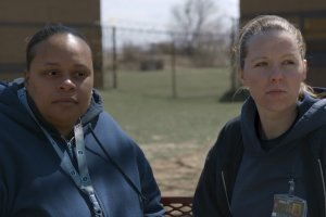two incarcerated woman sitting on a bench