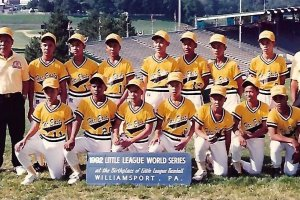 The 1992 Little League World Series Champion team from the Philippines pose in front of the baseball stadium in yellow jerseys and hats. Their coaches stand on either side of the players.
