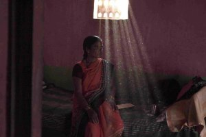 An Indian woman in a sari sits on a couch before a window. Light rays stream through the window's elaborate design