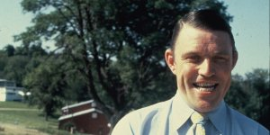 A Middle-aged White man smiles in a blue button-up and yellow tie in front of a rural set of houses.