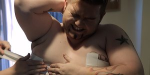 Donnie's face winces as tape is applied across his breast in a medical procedure.