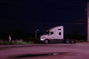 still of female truck driver starring at their truck in the middle of the night