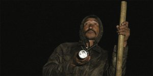 A man holds a wooden staff in the dark.