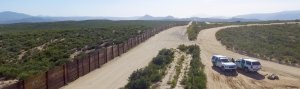 The US-Mexico border, patrolled by the green Border Patrol SUVs