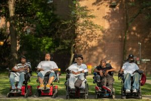 Five Black and brown men (from left to right: Vince, Jay, Tito, Pete and Var) sit in wheelchairs outside, lined up in a straight horizontal line facing the camera. They wear T-shirts and sneakers and some wear baseball caps. They all look into the camera with serious expressions.