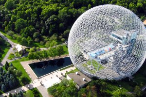 A geometric steel dome sits on a green landscape.