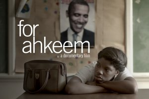 main character Daje rests her head on crossed arms at desk with bookbag and photo of Obama behind on wall