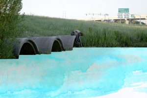 young boy sitting on top of one of three drainage tunnels expelling blue water color paint