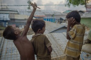 Three young boys living in a refugee camp on a rooftop playing