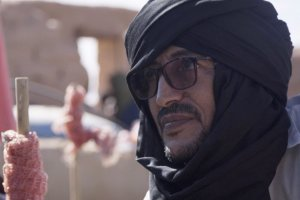 A man in a black headscarf and glasses looks into the distance.
