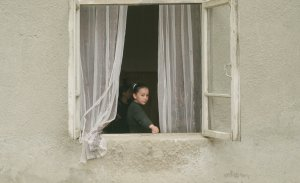 A young girl stares out the open window of a rustic stone building