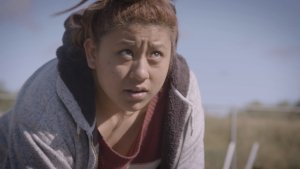 A Latina teenager leans over in a field, tilting her head upwards and looking away from her harvesting work.