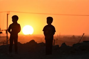 Two silhouetted children stand before the setting sun.