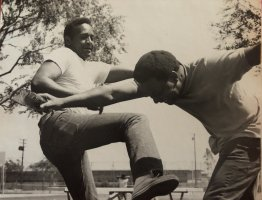 A black and white photo of two African-American man showcasing their stunts.