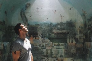 A man is looking up in front of a wall painting.