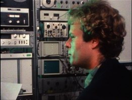 Ken Kelley stares in profile, surrounded by towers of sound recording equipment.