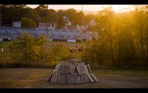 a pile of woodpallets sits on a hill above a pop-warner football practice at sunset.