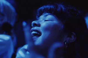 Latina woman dances to music amongst a crowded concert audience, in blue light.