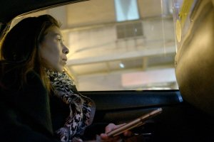 Chinese-American woman holds her phone in her hand while staring out the window of a taxi cab.