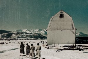 four monks walk outside of a white monastery covered in snow. Mountains break the horizon in the distance.